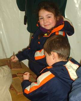 children trying out their skills at Roman tablet writing